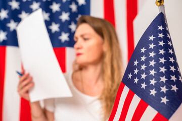 Election USA. Voter with a ballot paper in background. USA flag on blurred background. Election of President of USA. Woman is holding a ballot paper and a pen. Elections in United States of America.