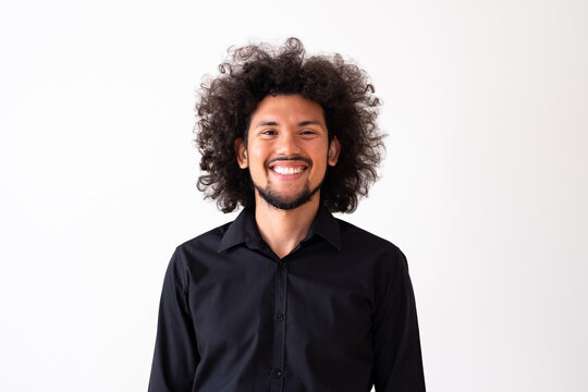 Latin American model in black shirt with big curly hair and beard, neutral background