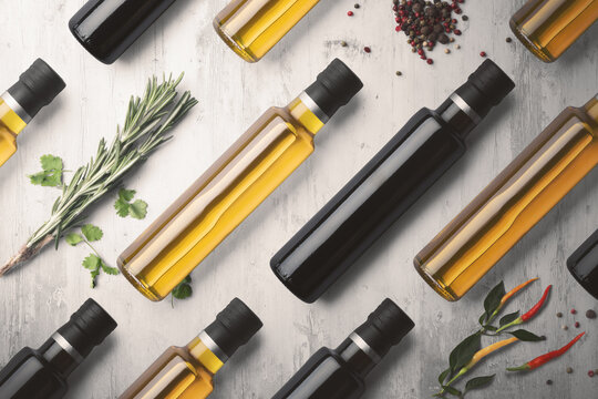 Bottles of virgin olive oil and balsamic vinegar aligned on a white wooden background with peppers, chilli and herbs