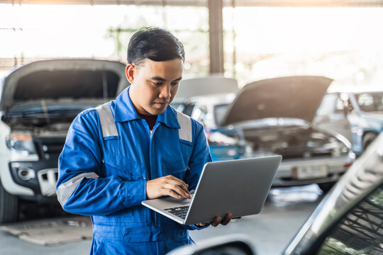 Mechanic Asian man using laptop computer examining tuning fixing repairing car engine automobile vehicle parts using tools equipment in workshop garage support and service in overall work uniform