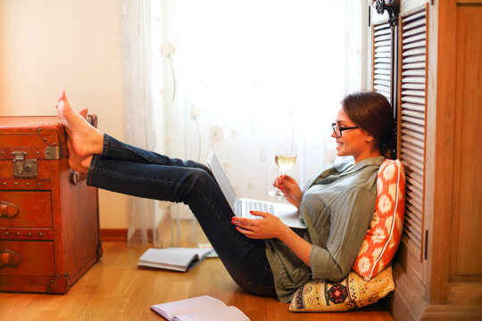 Crop freelancer with wine using laptop