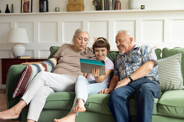Grandfather and grandmother with their granddaughter communicate via video communication with parents