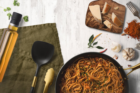 Top view kitchen scene showing a pan full of spaghetti bolognese surrounded by parmesan cheese of a chopping board, olive oil, a serving spoon and herbs and spices.