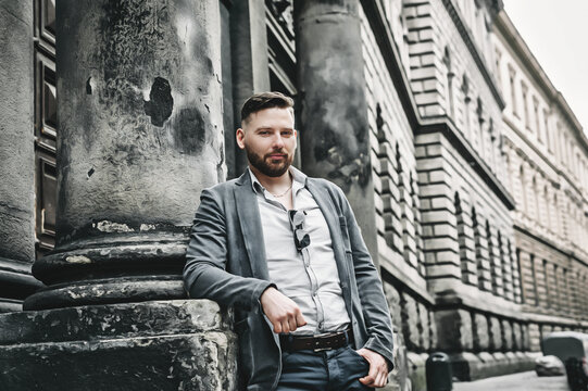 Сonfident mature businessman standing near office building. Handsome bearded man 30 years old.