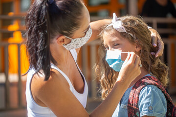 A mother and her daughter use a protective mask when returning to school during the COVID-19...