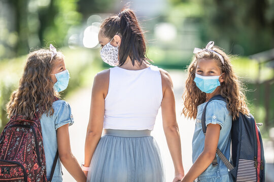 A mother and her twin daughter use a protective mask when returning to school during the COVID-19 quarantine