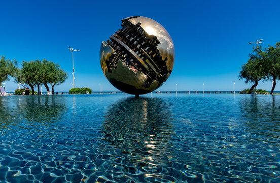 PESARO, ITALY - 21 AUGUST 2020: Grande Sphere by Arnaldo Pomodoro reflected in the water in Piazza della Libertà in Pesaro
