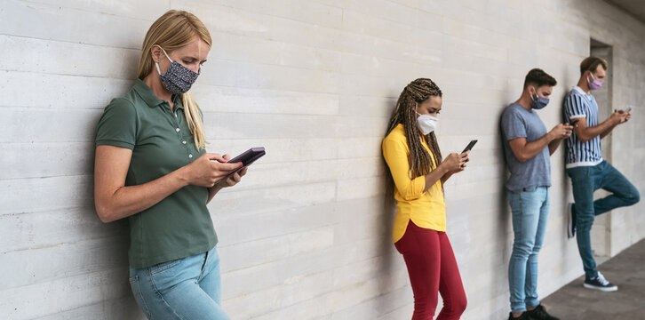 Young people wearing face mask using mobile smartphone outdoor - Multiracial friends having fun with new technology social media app during corona virus outbreak - Youth millennial lifestyle concept