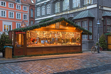 Luneburg, Germany. Market stall with Christmas gingerbreads, roasted almonds, cotton candy and sweets at Am Sande square close to historical building that houses the Chamber of Commerce and Industry.