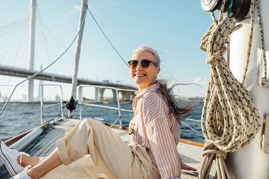 Happy mature woman wearing sunglasses on a sailboat and looking at camera. Senior female sitting on yacht deck and enjoying the voyage.