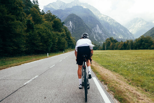 Athletic fit cyclist on professional carbon road bike ride on tarmac road towards mountain in distance. Man on bike wears white lightweight jersey and protective helmet. Outdoors sports activity