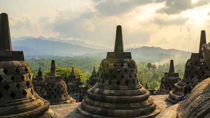Glorious sunset at Borobudur Temple in East Java, Indonesia. Orange sky over the hills, green jungles and stupa, travel destination, UNESCO World Heritage Site