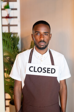 Young serious waiter of African ethnicity with paper saying closed on his neck
