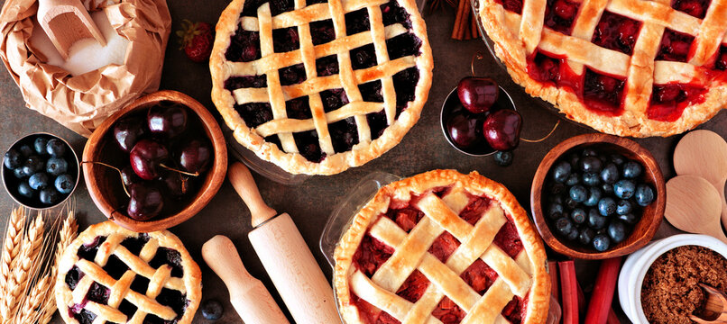 Baking scene with a variety of homemade fruit pies. Top view over a wood banner background.