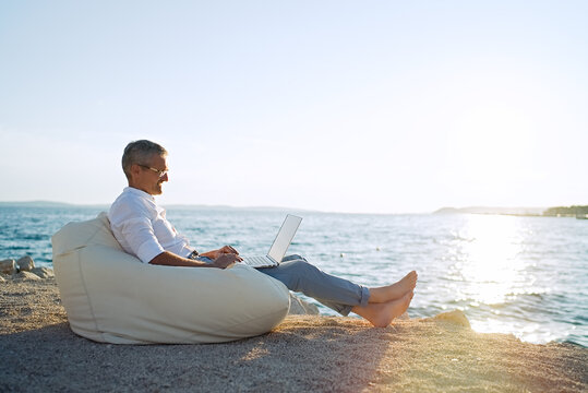 Senior man working on his laptop lying on deck chair on the beach during sunset