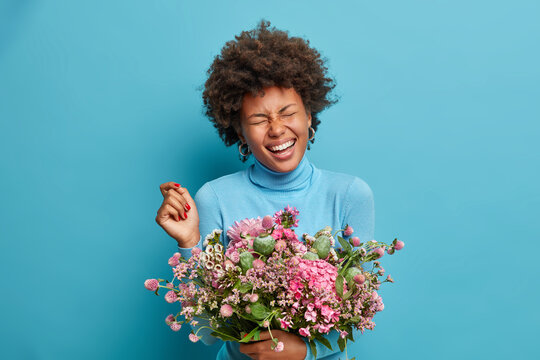 Joyful female florist poses with beautiful bouquet of flowers, laughs happily, has closed eyes, wears blue poloneck, poses indoor. Afro American woman gets surprise from husband on birthday.
