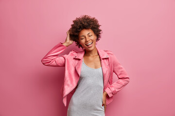 Foto auf Leinwand Vogel auf Asten Amused carefree young Afro American woman with closed eyes, enjoys awesome day off, dressed in stylish clothes, smiles broadly, isolated on pink background, feels lucky, free and successful.