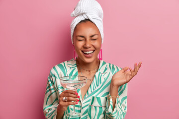Horizontal shot of happy woman with natural beauty, dark skin, well cared complexion, enjoys domestic atmosphere, drinks cocktail after taking bath, dressed in comfortable clothes, relaxes at home