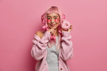 Horizontal shot of satisfied young Asian woman enjoys beauty skin treatments and hairstyle activity, holds delicious glazed doughnut, wears hair curlers dressed in warm clothes poses against pink wall