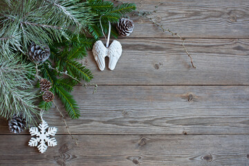 Christmas wooden background, pine and fir branches, cones, angel wings and snowflake decor. Space for text and congratulations.