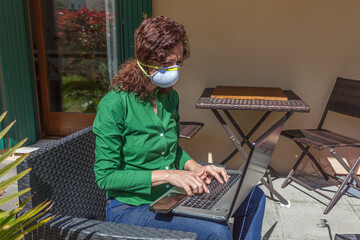 Woman with antivirus mask working with laptop in a garden. People life during the pandemic