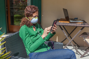 Woman sitting in a garden with antivirus mask looking at cellphone searching news. People life during the pandemic