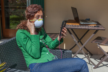 Scared woman sitting in a garden with antivirus mask looking at cellphone searching news. People life during the pandemic