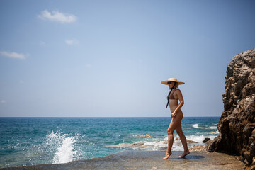 Photo sur Plexiglas Ane A beautiful girl in a swimsuit with a golden tan in a hat walks along the rocky coast near the blue sea. Summer sunny day by the sea. Vacation concept