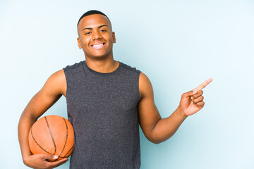 Young colombian man playing basketball isolated smiling and pointing aside, showing something at blank space.