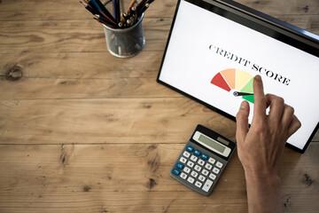 online finances hand pressing credit score button on tablet