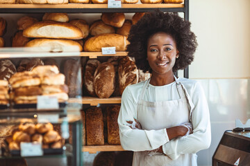 Portrait of positive African American young woman working in own Bakery shop, looking at camera with toothy smile. Pretty baker smiling at camera. Small Bakery shop owner standing in front of store