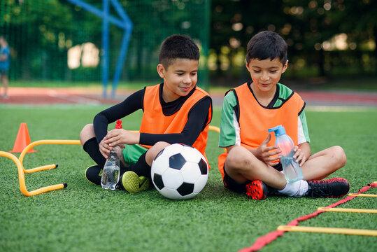Two happy teen boys in football uniforms having a rest on the sport field and enjoying fresh water in the break.