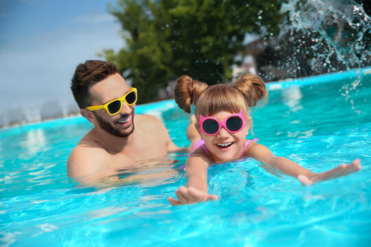 Father and daughter having fun in swimming pool. Family vacation