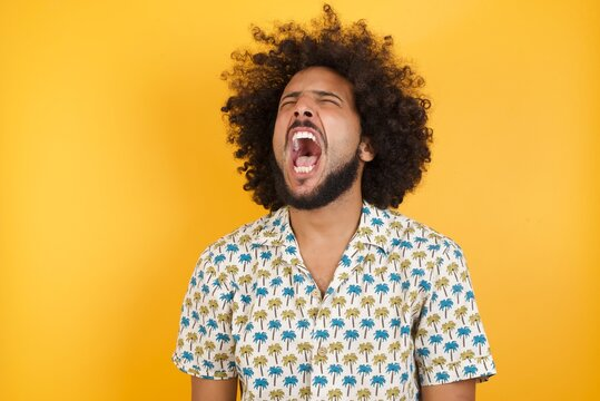 Young man with afro hair wearing hawaiian shirt standing over yellow wall angry and mad screaming frustrated and furious, shouting with anger. Rage and aggressive concept.