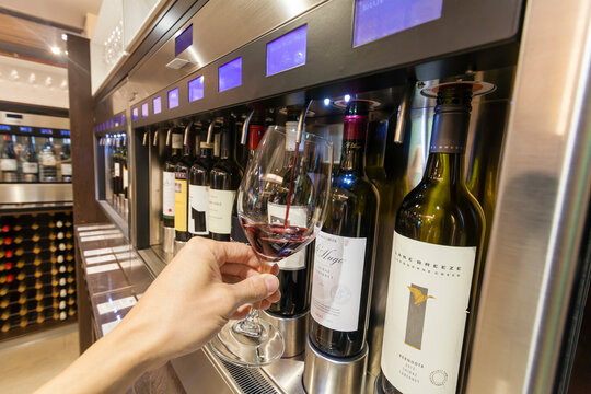 Adelaide, Australia - March 14, 2015: Tourist filling a glass with red wine for wine tasting inside a the National Wine Centre of Australia in Adelaide.