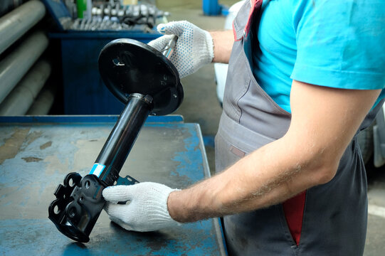 In the hands of a car mechanic, a new shock absorber strut. Repair and maintenance of the car in the service center. The technical condition of the shock absorber is checked before installation.