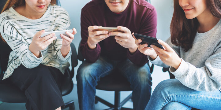 Group of young people using and plying games on mobile phone while sitting together