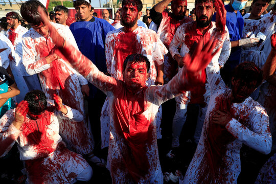 Iraqi Shi'ite Muslims bleed after hitting their foreheads with swords and beating themselves during a ceremony marking Ashura, the holiest day on the Shi'ite Muslim calendar, amid the spread of the coronavirus disease (COVID-19), in Baghdad