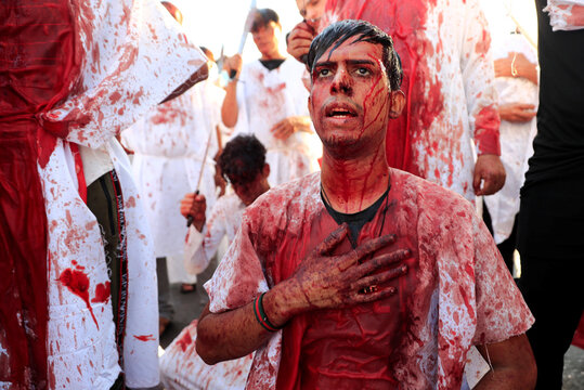 A Shi'ite Muslim man bleed after hitting his forehead with sword and beating themselve during a ceremony marking Ashura, the holiest day on the Shi'ite Muslim calendar, amid the spread of the coronavirus disease (COVID-19), in Baghdad