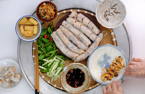 Vietnamese woman hand prepare breakfast, homemade vegan rice noodles roll from rice batter, delicious vegetarian stuffed dish