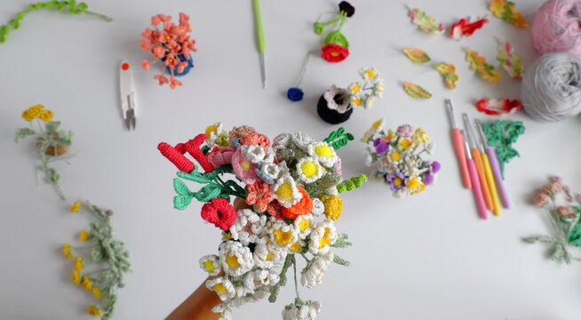 Woman hand hold handmade crochet product, bunch of colorful flower, beautiful artwork diy  in leisure activity