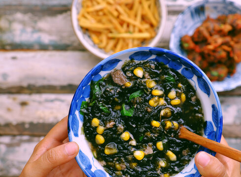 Woman hand hold seaweed with corn soup bowl for vegan meal on food background