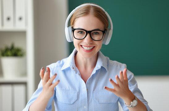 Friendly teacher in headphones looking at camera.