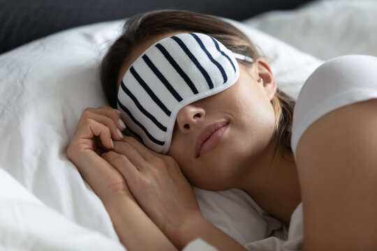 Close up peaceful young woman wearing stripped mask sleeping on side, resting on soft pillow under warm duvet, enjoying fresh white cotton bedclothes, relaxing in cozy bed at home or in hotel