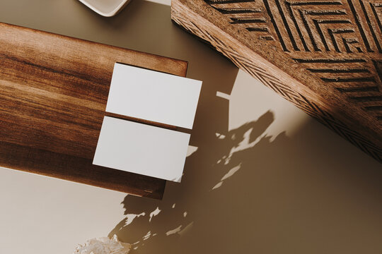 Blank paper sheet cards with mockup copy space, wooden tray, casket and dry flowers with sunlight shadow on beige background. Minimal business brand template. Flat lay, top view