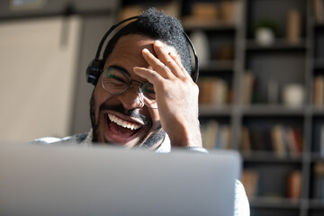 Laughing African American man wearing headphones looking at laptop screen close up, positive young male wearing glasses chatting online, making video call, watching funny movie or playing game