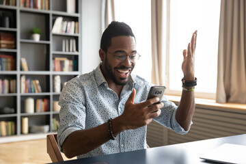 Foto auf Leinwand Vogel auf Asten Happy surprised African American man excited by good news, using phone, positive young businessman holding smartphone, looking at screen, reading unexpected message or email, lottery win