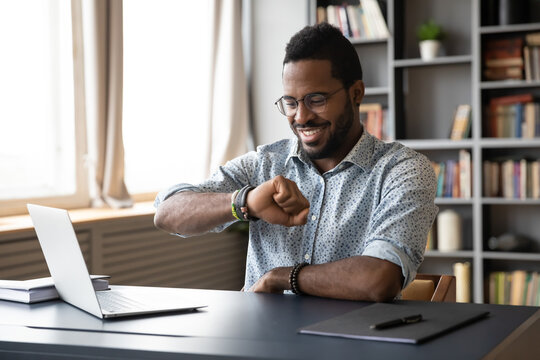 Smiling African American businessman wearing glasses checking time, looking at wristwatch on hand, positive happy young man entrepreneur sitting at desk, planning work, task management concept