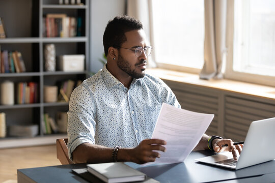 Serious confident African American man wearing glasses using laptop, holding document, paperwork, focused businessman accountant working on financial report, student writing research work