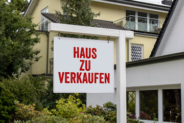 Wooden sign in front of a house with message For Rent, For Sale, and the german words for sale - zu verkaufen